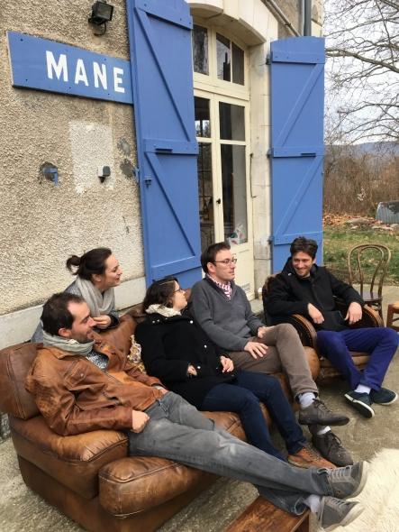Photographie d'une partie de l'équipe de Graines de Mane à la gare de mane assis devant la gare sur et autour d'un canapé et un fauteuil